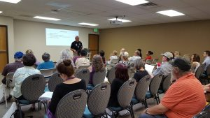 Seniors, caregivers and professionals listen as Colorado Springs Police Det. Charles Szatkowski presents Friday, June 15, for World Elder Abuse Awareness Day at Silver Key Senior Services.