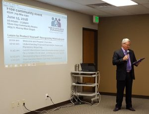 Seniors, caregivers and professionals listen as El Paso County Department of Human Services Deputy Executive Director Chris Garvin speaks Friday, June 15, for World Elder Abuse Awareness Day at Silver Key Senior Services.