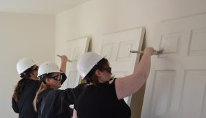DHS volunteers paint doors in a Pikes Peak Habitat for Humanity home in Fountain.